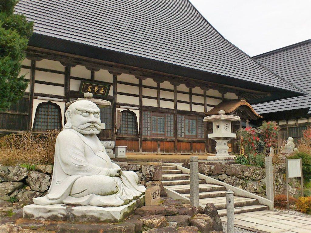達磨大師の石像と全長寺本堂