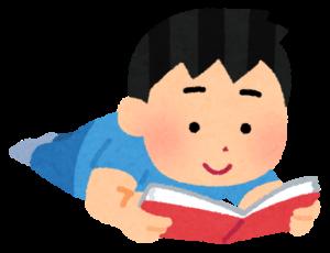 うつ伏せで本を読む男性