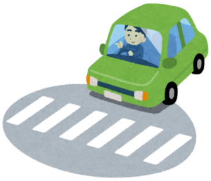 横断歩道の手前で一旦停止する自動車