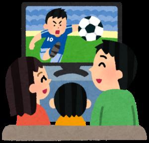 テレビでサッカーを観る家族
